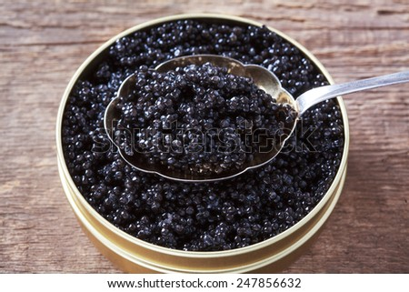 Tin can and a spoon with natural sturgeon caviar on a wooden background. Selective focus and space for text - stock photo