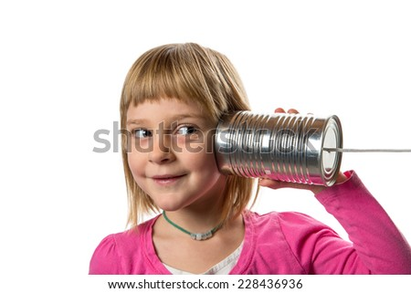 Tin Can Phone - Listening.  Young girl listening to tin can / string phone.  Isolated against white background.  Copy space to left. - stock photo