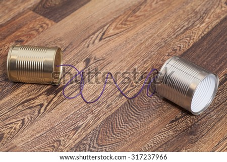 Tin Can Phone on Wooden Background.Communication concept - stock photo