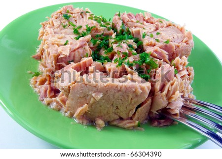 Tinned tuna with some parsley on a green plate isolated on white - stock photo