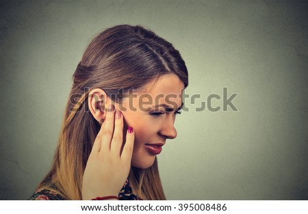Tinnitus. Closeup side profile sick young woman having ear pain touching her painful head isolated on gray background - stock photo