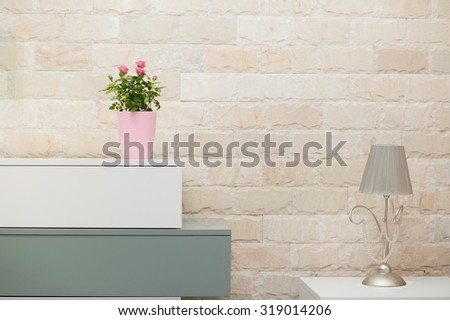 Tinny roses in pink vase on closet decorates living room - stock photo