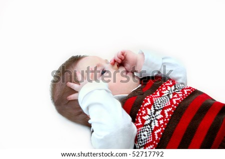 Tiny baby lays on all white floor and sucks his thumb.  He is totally absorbed in himself.  His vest is brown and red knit and covers a white long-sleeved turtle neck shirt. - stock photo