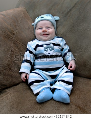 Tiny baby lays on couch in his home.  He is smiling happily and relaxing in the support of his family. - stock photo