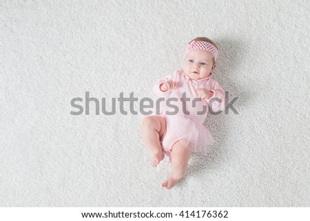 Tiny baby lies on his back on the floor and looking up. - stock photo