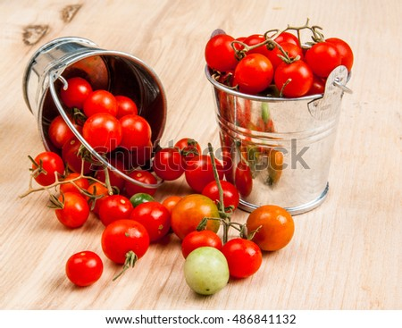 Tiny baby tomatoes in a small bucket on a wooden table