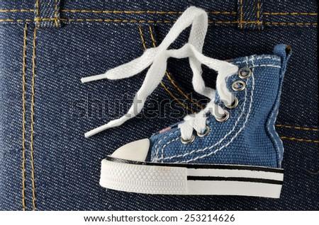 tiny blue shoe on denim background, horizontal - stock photo