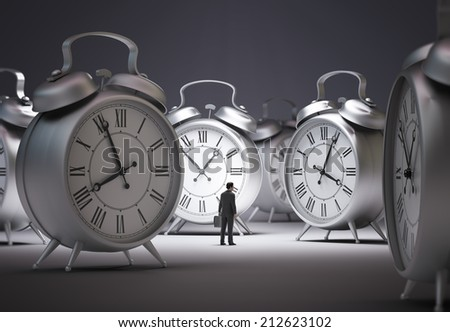 Tiny businessman surrounded by alarm clocks - stock photo