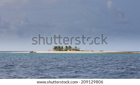 Tiny Caribbean Island with White Sand Beach, Palm Trees and  Umbrellas - stock photo