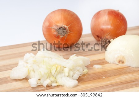 Tiny chopped onions on a kitchen wooden board. - stock photo