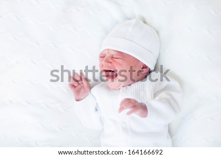 Tiny crying newborn baby ni a white knitted hat and jacket - stock photo