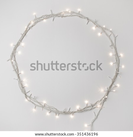 Tiny elegant christmas lights border. Round shape made with rice bulb series on white background. - stock photo