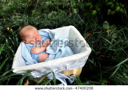Tiny infant lays in a wicker basket surrounded by the forest and leaves of deep green.  He is stretching and making a grimace. - stock photo