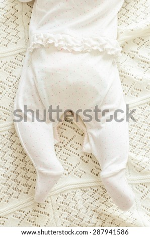 Tiny little newborn daughter baby's feet in nice white spotted romper suit lying on the background of white woolen blanket on a bed at home, top view.  - stock photo