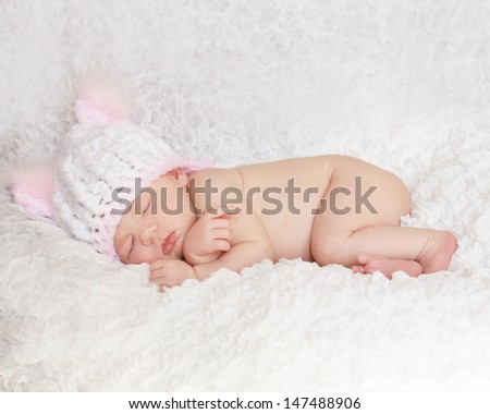 Tiny newborn baby sleeping wearing just white knitted hat - stock photo