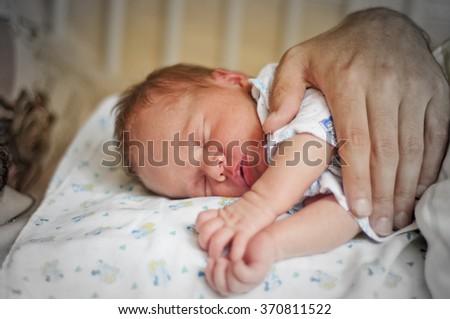 Tiny newborn baby sleeps on hand of his father - stock photo