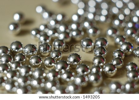 Tiny silver balls on a tabletop - stock photo