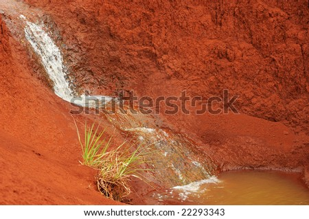 Tiny waterfall spilling into a basin among red, desertlike rocks