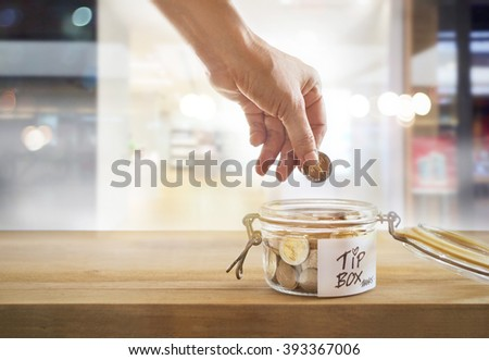Tip box, coin in the glass bowl in cafe front of mirror, warm color and soft concept - stock photo