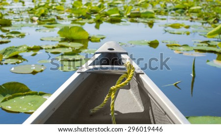 Tip of a canoe sailing among lily pads. Pelee point conservation area, Ontario, Canada - stock photo