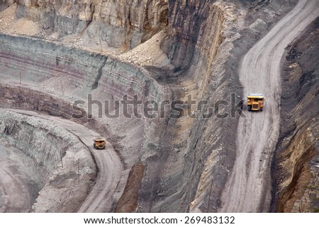 Tip-trucks on the road in open mine - stock photo