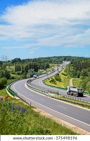 Tipping lory and trucks traveling on the asphalt highway with electronic toll gates in a wooded landscape. View from above. Sunny summer day. - stock photo