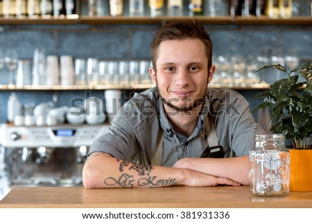 Tips are welcome. Handsome smiling barista leaning on the counter in his coffee shop smiling cheerfully - stock photo