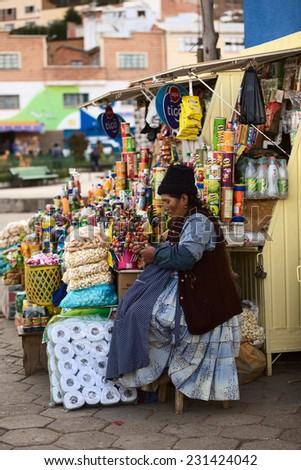TIQUINA, BOLIVIA - OCTOBER 16, 2014: Unidentified woman sitting at a snack stand and doing crochet at the main square on October 16, 2014 in San Pedro de Tiquina, Bolivia