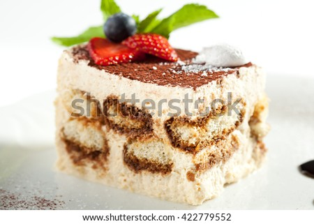 Tiramisu - Classical Dessert with Cinnamon and Coffee. Garnished with Strawberry and Mint - stock photo