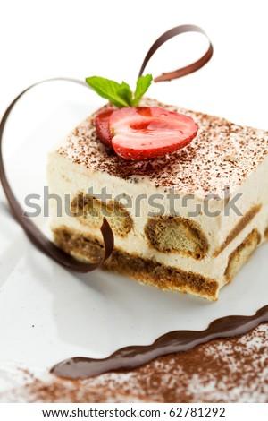 Tiramisu - Classical Dessert with Cinnamon and Coffee. Garnished with Strawberry and Mint - stock photo