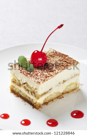 Tiramisu - Classical Dessert with Coffee on white plate. Garnished with Cherry and Mint.