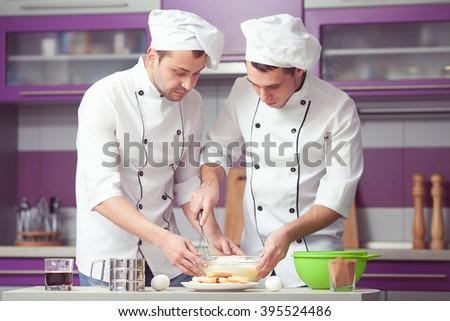 Tiramisu cooking concept. Portrait of two working men in cook uniform making italian dessert in modern kitchen. Indoor shot - stock photo
