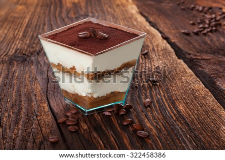 Tiramisu dessert with coffee beans on wooden textured table. Traditional tiramisu dessert, rustic, country style. - stock photo