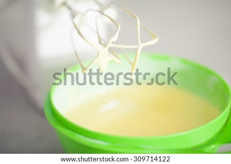 Tiramisu ingredients concept. Mixing egg yolks with sugar into cream in bowl with motor mixer, baking cake. Close up. Indoor shot - stock photo