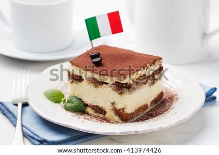 Tiramisu, traditional Italian dessert on a white plate with Italian flag - stock photo