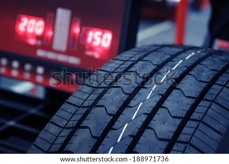 Tire check on balancing machine.Blue toned photo - stock photo