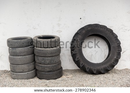 tire, maintenance, service and motor transport concept - close up of wheel tyres stored near wall - stock photo