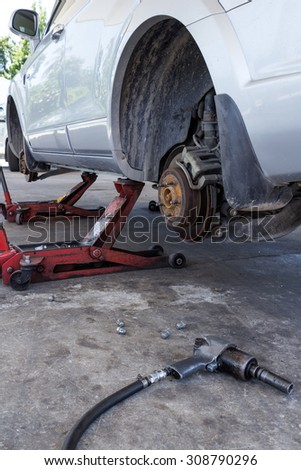 Tire replacement service fitting by hand jack with pneumatic wrench - stock photo