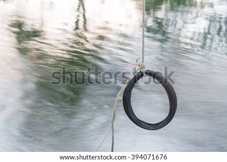 Tire swing hanging from a tree , Waiting for Summer on the river nature jumping ( blur blurred river background) - stock photo