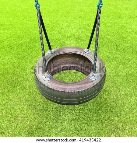 Tire swing on green grass background. Kids playground.