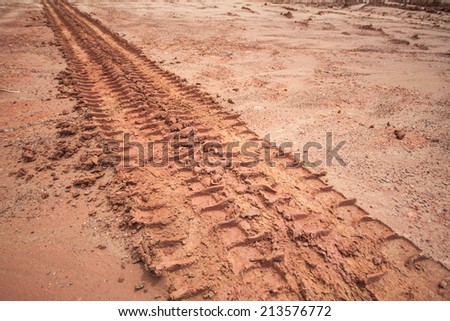 Tire tracks on a muddy road in the countryside.