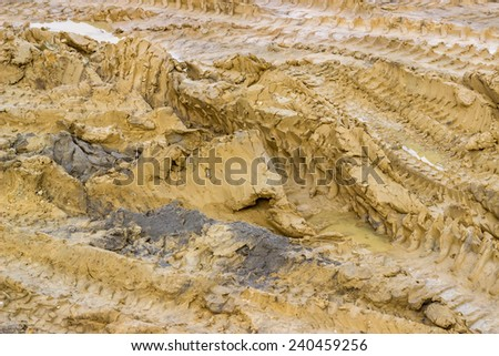 Tire tracks on the ground and puddles, background. Selective focus. - stock photo