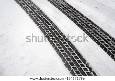 Tire tracks - tire marks in the light snow in winter - stock photo