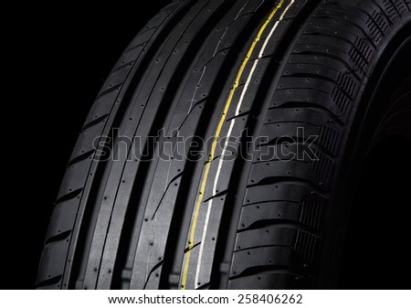 tire with asymmetric tread on a black background - stock photo