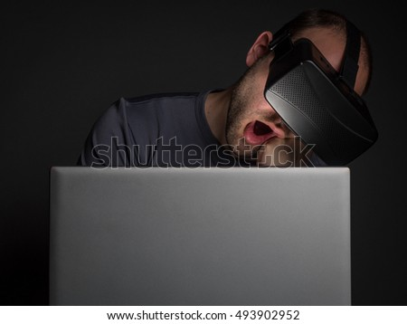 Tired addicted man to technology  using virtual reality headset at night. Technology addiction and mental disorders concept.