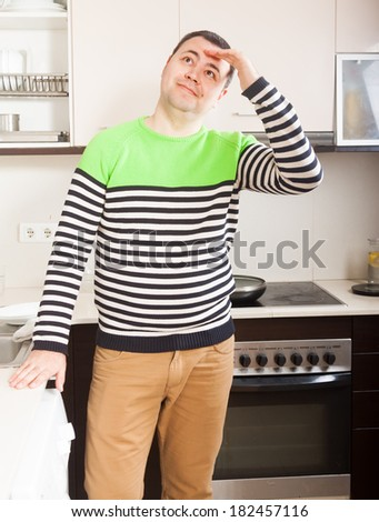 tired adult man standing in  kitchen - stock photo
