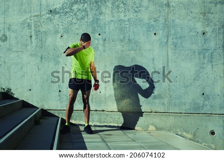 Tired after intensive evening jog athletic runner resting on concrete wall background at sunny day, attractive sporty man taking break after evening run, fitness and healthy lifestyle concept - stock photo