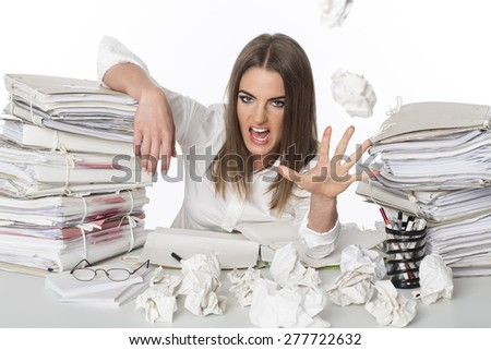 Tired and angry business woman et the desk - stock photo