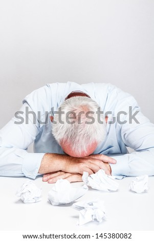 Tired and exhausted businessman in office - stock photo