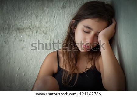 Tired and lonely hispanic girl sitting next to a dirty wall with her eyes closed - stock photo